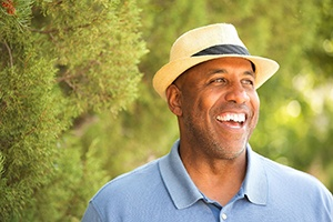 older man in blue shirt and fedora smiling