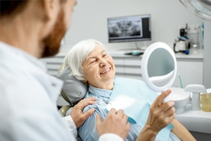 woman smiling in dental mirror