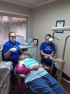 Two team members laughing with patient