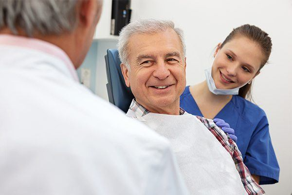 Mature man speaking to dentist