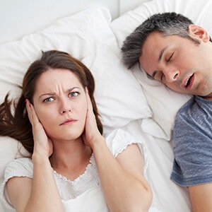 Woman covering her ears next to snoring man