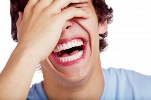 teenage boy laughing covering eye