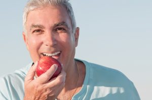 smiling mature man eating apple
