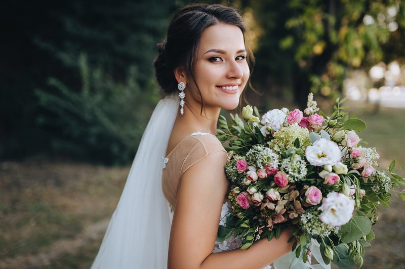Bride smiling in wedding dress with bouquet
